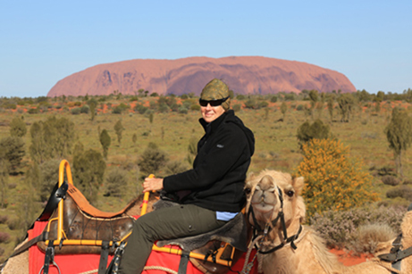 Gwenda riding a camel with Olarooo in the background